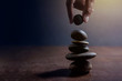 Quadro Balance concept between of Life and work present by Hand setting a natural zen rock stone on Stack, Side view and Dark light