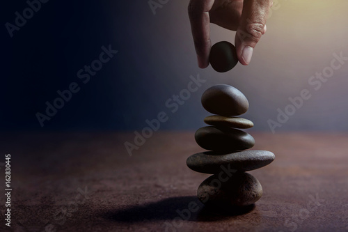 Papiers peints Spa Balance concept between of Life and work present by Hand setting a natural zen rock stone on Stack, Side view and Dark light