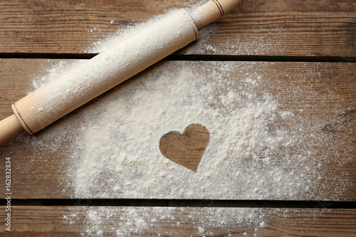 Heart drawn on flour and rolling pin on wooden background - 162832834
