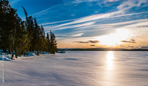 sunset over frozen lake with pearlescnet clouds