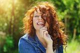 jeune et jolie femme rousse souriante dans nature avec fleur bleue
