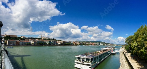 Sunny panorama cityscape with a cloudy blue sky of the capital of Hungary -Budapest- in Europe with a cruise boat on the green Danube river