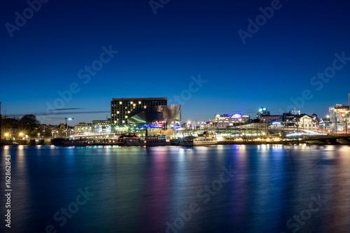 Stockholm Waterfront på kvällen med sin aluminium fasad och turistbåtarna på Klara Mälarstrand nedanför