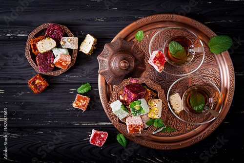 Bowl with various pieces of turkish delight lokum and black tea with mint on a dark wooden background. Flat lay. Top view