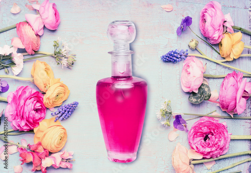 Bottle of perfume and flowers at shabby chic background, top view. Floral cosmetic and beauty concept.