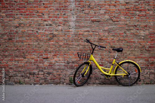 Yellow Bicycle by the Brick Wall