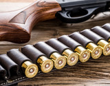 Pump action shotgun, 12 mm hunting cartridge on the wooden table. - 162886619