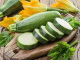 Zucchini with slices and zucchini flowers on a wooden table. - 162886652