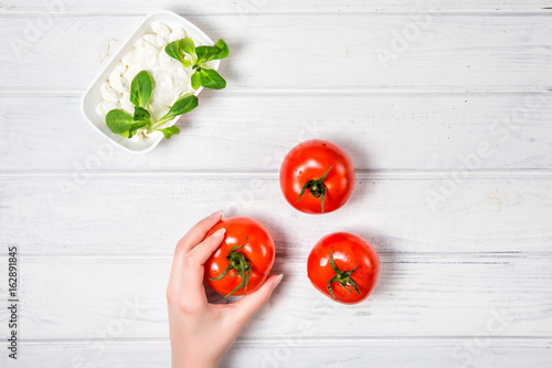 Female hand holding tomatoes. A vegetarian Breakfast.
