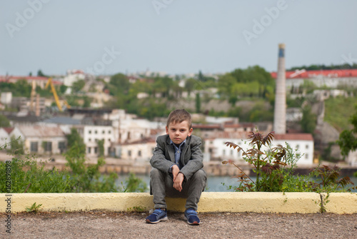 Sad little boy sitting on the curb with sea port background