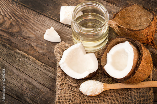 Half of coconut, pieces of coconut, coconut flakes and coconut glaas jar