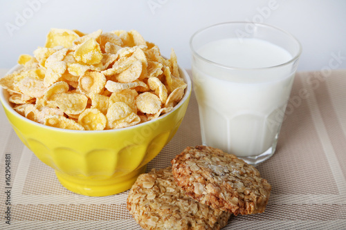 Cornflakes in bowl with glass of milk and cookies