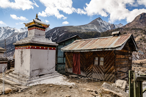 Tibetan stupa with rural wooden house with Black mountain with snow on the top is background at Thangu and Chopta valley in winter in Lachen. North Sikkim, India.
