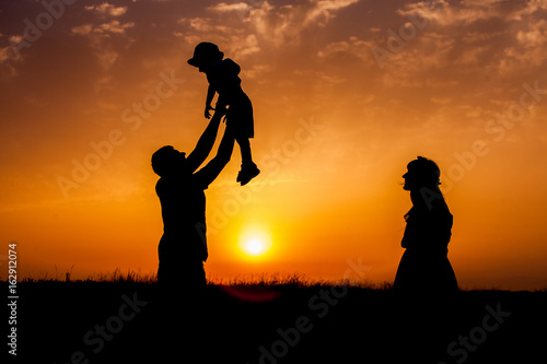 Family silhouettes in nature. We are happy family. silhouette of happy family father mother and son playing outdoors at sunset.