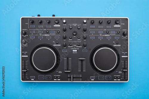Modern DJ mixer on blue background Poster