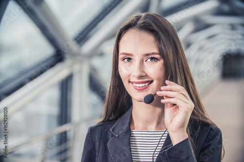 portrait of a female businessman with headset smiling in call center