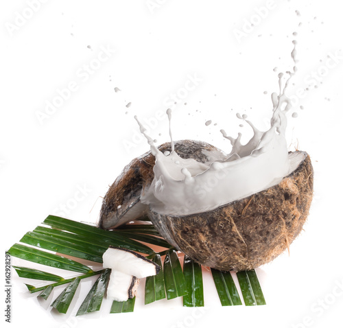 Cracked coconut with milk splash and leaf on white background.