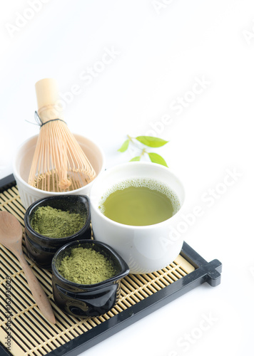 Green matcha tea in a bowl and bamboo whiskon, isolated on white