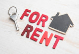 "Symbol of the house with text ""FOR RENT"" and key on white wooden background"