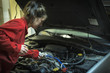Female mechanic checking the oil level of a car