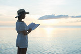 A beautiful young Asian woman in a vintage dress and Summer hat stands reading a book with an idyllic beach sunset. Beauty in nature, dreamlike, imagination and wonderlust concepts. - 162951658