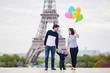 Happy family of three in Paris near the Eiffel tower