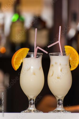 Milkshake with orange and ice is on the table