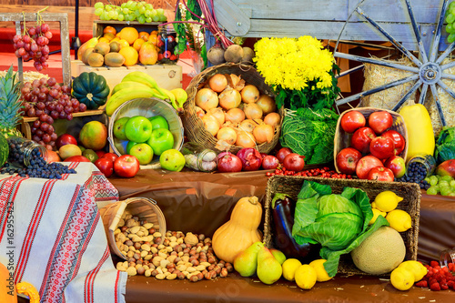 Set ripe healthy foods consisting of vegetables and fruits lying on the wooden table closeup