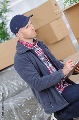 courier holding a clipboard in the background packages