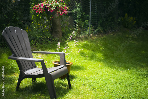 Fotobehang Tuin Simple adirondack chair on grassy area with potted plant and hanging basket of flowers