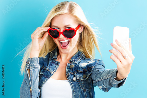 Plakát Young woman taking a selfie on a blue background