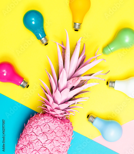 Painted pineapple with light bulbs on bright colored paper background - 162977087
