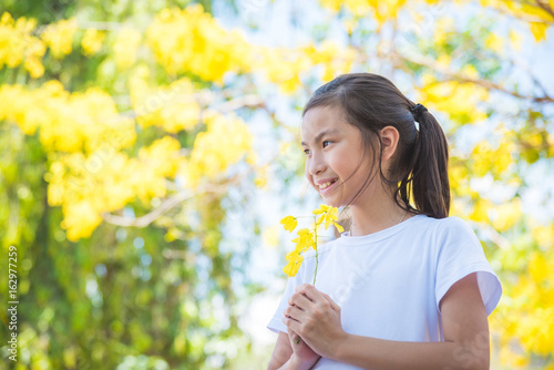 Young asian girl holding flower and smiles in park