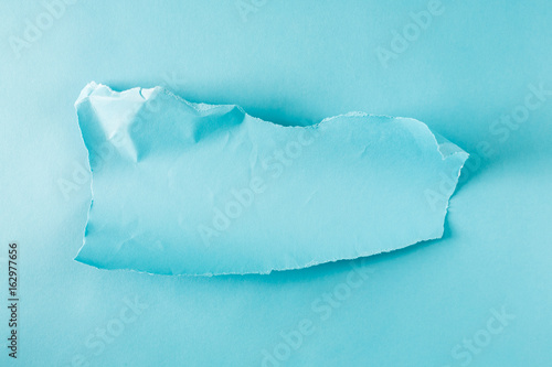 Torn piece of blue paper on a blue background