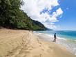10 year old boy walking over golden sand on sunny Ke'e Beach, Kauai, Hawaii