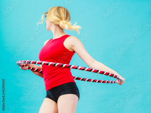 Fit woman with hula hoop doing exercise