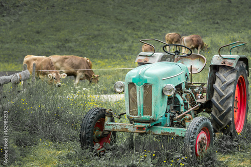 Old tractor on meadow. Beautiful mountain view in the Alps