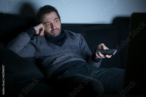 Plagát Bored man watching television at night