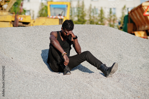 Attractive black african american guy in black muscle shirt posing on the pile of gravel in industrial zone.