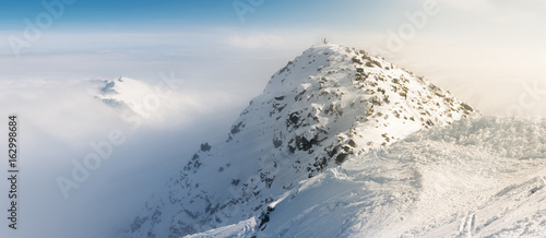 Chopok peak on snowy winter time, above the clouds with sun rays effect.