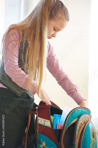 Mädchen packt Schulrucksack aus