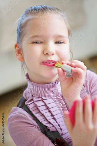 Mädchen schminkt ihre Lippen mit Lippenstift