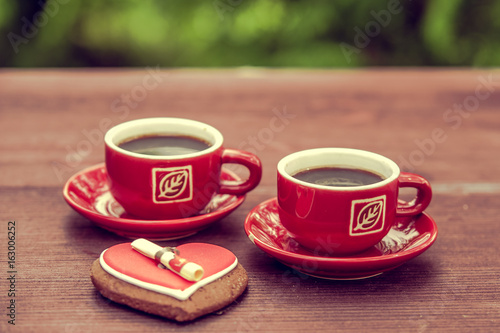 Background on a theme of coffee with place for text. Two cups of coffee, espresso, Heart shaped cookies, wooden table.
