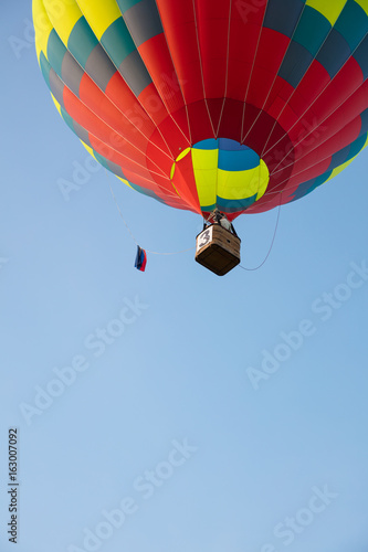 Bright balloon and basket in blue sky bottom view - 163007092