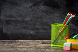 School supplies on wooden table and blackboard background. Back to school concept. Copyspace.