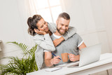 happy woman hugging man that sitting at workplace at home