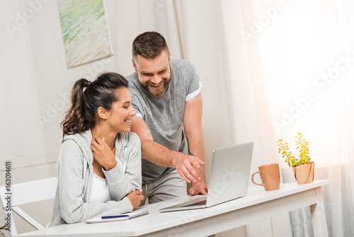 portrait of cheerful couple together working on laptop at home