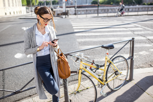 Portrait of a young businesswoman standing with phone near the bicycle outdoors on the street