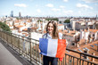 Young woman holding a french flag on the city background in Lyon old town in France - 163017087