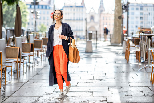 Lifestyle portrait of a french woman walking with bag and baguette on the street with cafes in Lyon city Photo by rh2010